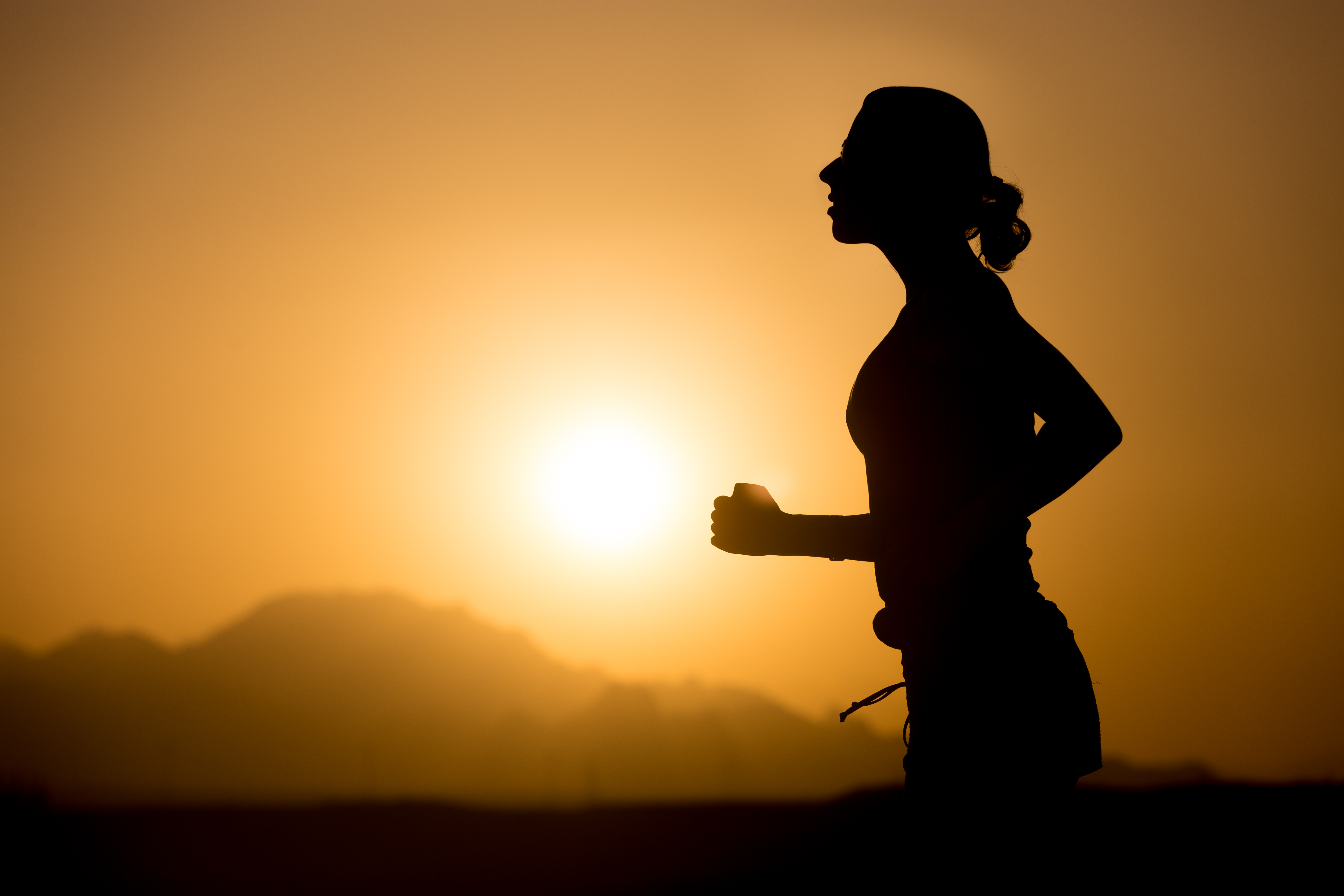 Profile silhouette of young sporty woman jogging against colorful picturesque mountainous landscape with rising or setting sun, copy space
